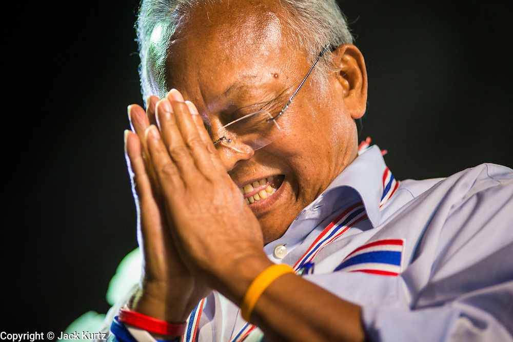 24 JANUARY 2014 - BANGKOK, THAILAND:  SUTHEP THAUGSUBAN greets the crowd while he walks on stage before speaking at the Shutdown Bangkok Pathum Wan site. Shutdown Bangkok has been going for 12 days with no resolution in sight. Suthep, the leader of the anti-government protests and the People's Democratic Reform Committee (PDRC), the umbrella organization of the protests,  is still demanding the caretaker government of Prime Minister Yingluck Shinawatra resign, the PM says she won't resign and intends to go ahead with the election.   PHOTO BY JACK KURTZ