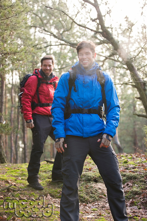 Happy male hikers looking away in forest