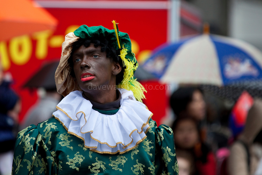 Participant dressed as Black Peter at Sinterklaas parade, Amsterdam Sinterklaas parade, Dam Square, Amsterdam, 14th November 2010. Sinterklaas, the basis for Santa Claus in other countries, arrives from Spain by boat,  accompanied by Black Peter, played by multitudes of white Dutch people in blackface - a tradition that evokes some controversy. Contrary to traditions of Santa Claus elsewhere, Sinterklass arrives by boat, then rides through the streets on his grey horse, Amerigo,  in mid-November, bringing in the Christmas season. The Zwarte Pieten (Black Peters) distribute sweets and gingerbread cookies to the crowd along the parade route.