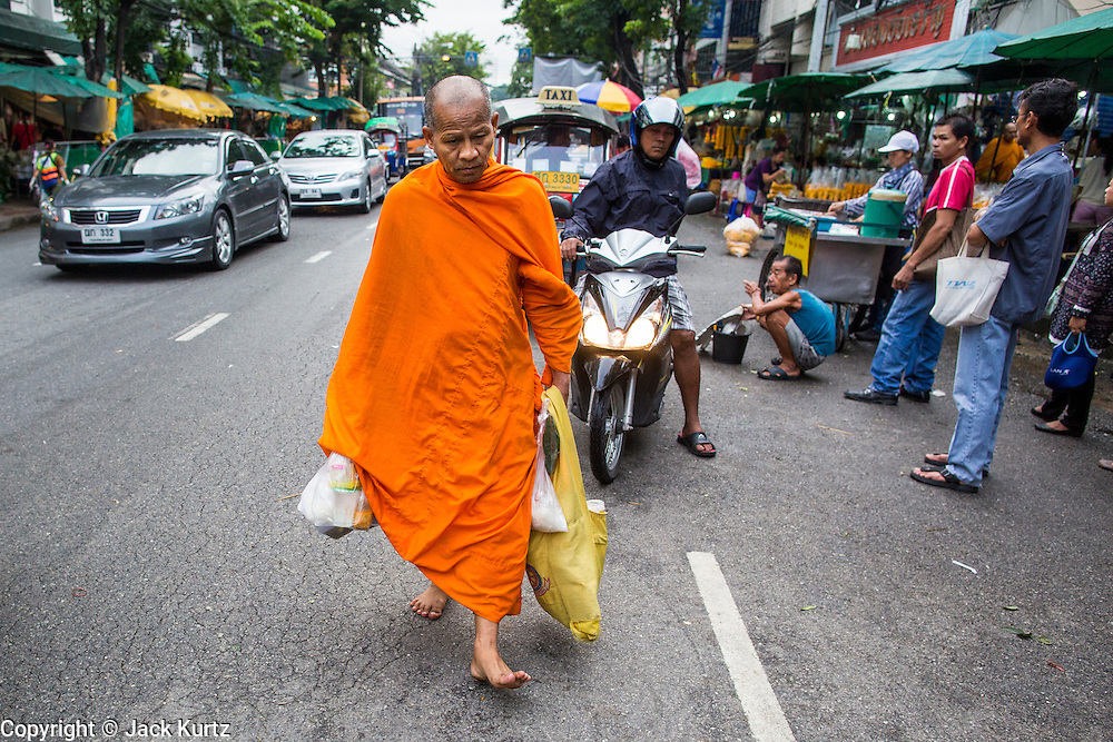 09 OCTOBER 2012 - BANGKOK, THAILAND: A Buddhist monk walks along Th Chak Phet (Th is the abbreviation for Thanon, the Thai word for street) in front of the flower market in Bangkok. The Bangkok Flower Market (Pak Klong Talad) is the biggest wholesale and retail fresh flower market in Bangkok. It is also one of the largest fresh fruit and produce markets in the city. The market is located in the old part of the city, south of Wat Po (Temple of the Reclining Buddha) and the Grand Palace.    PHOTO BY JACK KURTZ