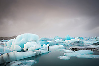 Jökulsárlón Glacial Lagoon, Southeast Iceland. A surfer wearing a we suite standing on one of the Icebergs.