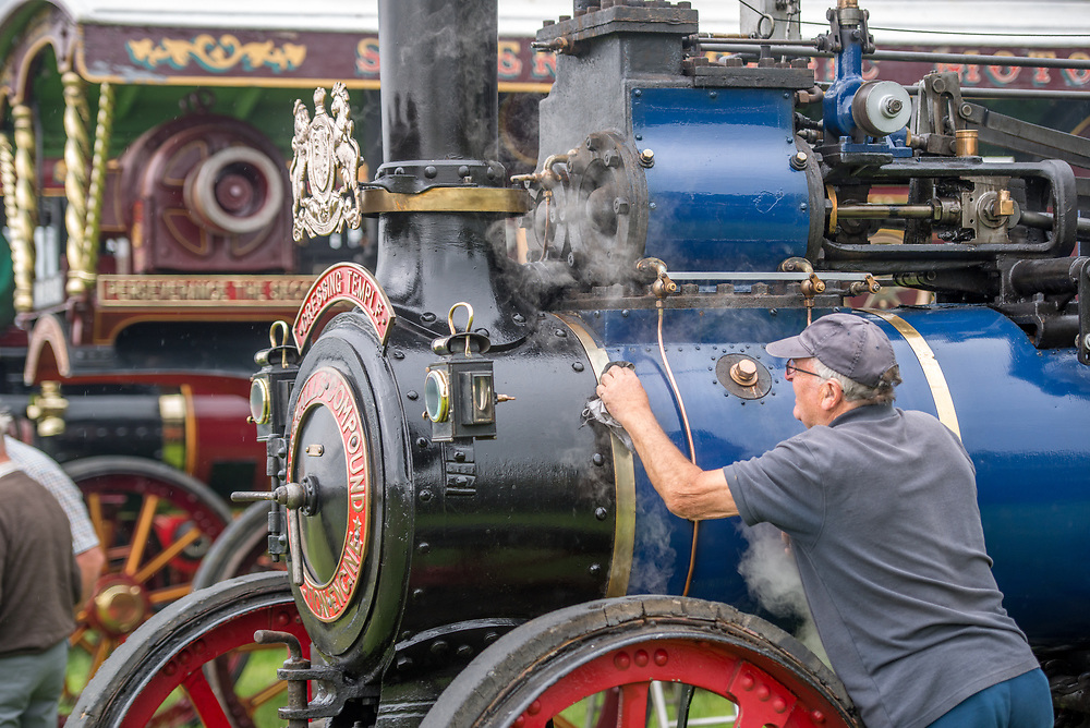 Mature male uses rag to polish steam engine tractor, Masham, North Yorkshire, UK