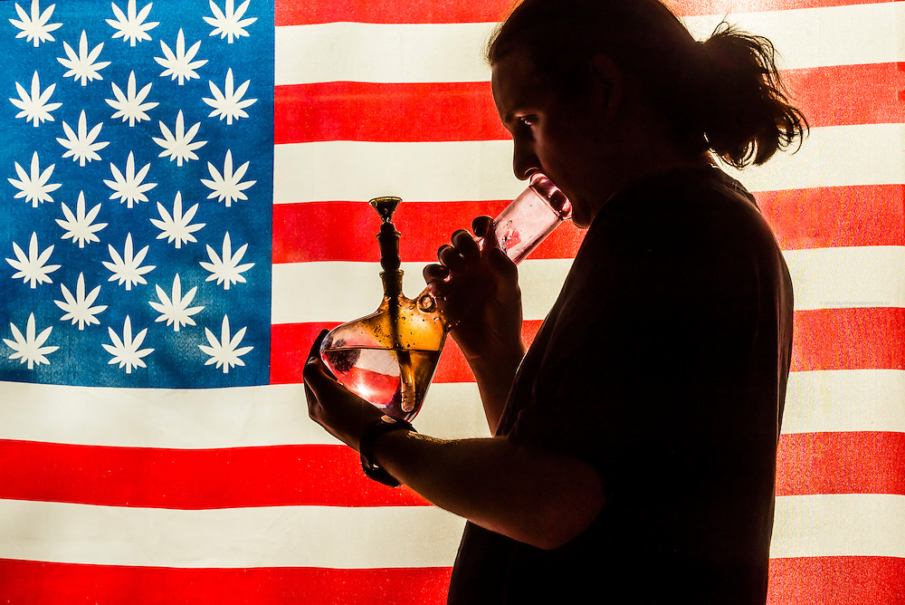 Man smoking bong with American marijuana flag i background, Littleton, Colorado USA.  Colorado was the first state to legalize the sale of marijuana for recreational use in 2014.