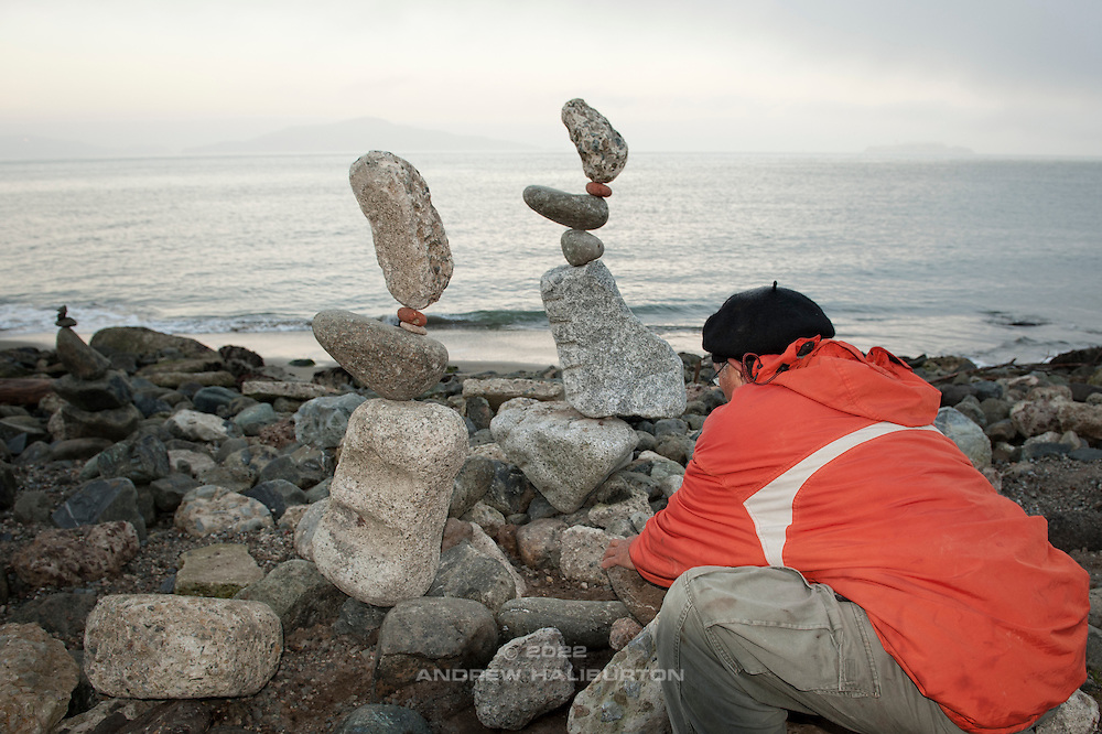 Bill Dan is a sculptor and performance artist specializing in rock balancing.  Golden Gate Bridge, San Francisco, California.