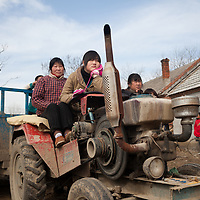 Locals watch a religious performance from atop a tractor.