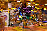 Child enjoying Merry-go-round carousel at Christmas fairground and market, Winter Wonderland, in Hyde Park, London