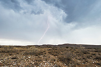 Lightning and heavy grey rain clouds over the arid Northern Cape, Rooipoort Nature Reserve, Northern Cape, South Africa