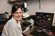 Dr. Gemma Casadesus Smith, a researcher in biological sciences, poses with some of her research into Alzheimer's Disease.