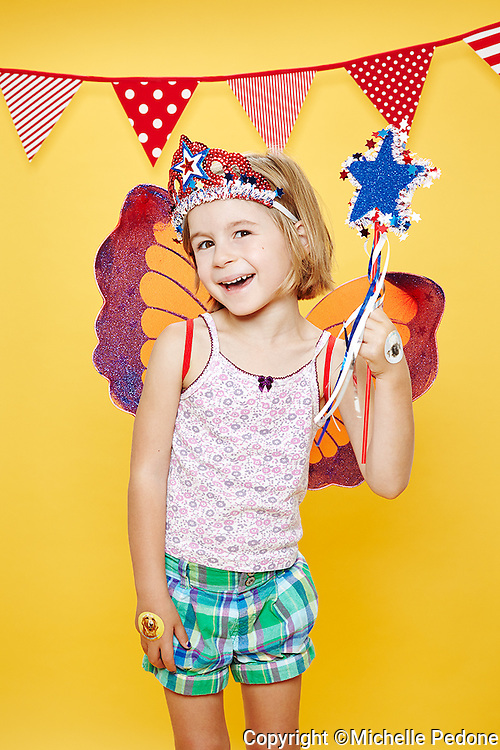 Blonde hair brown eyed little girl smiling wearing angel wings and a red white and blie tiara and magic wand. Photographed at the Photoville Photo Booth September 20, 2015