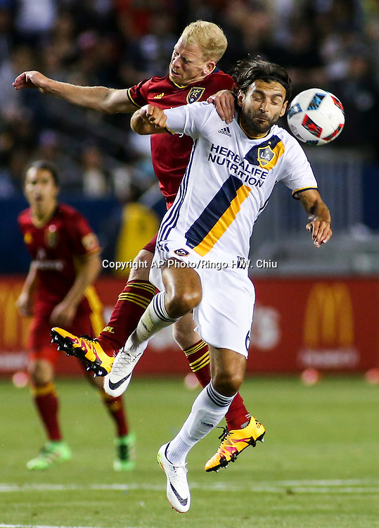 Los Angeles Galaxy midfielder Baggio Husidic, right, and Real Salt Lake midfielder Luke Mulholland battle for a all in the second half of an MLS soccer game in Carson, Calif., Saturday, April 23, 2016. The Galaxy won 5-2. (AP Photo/Ringo H.W. Chiu)