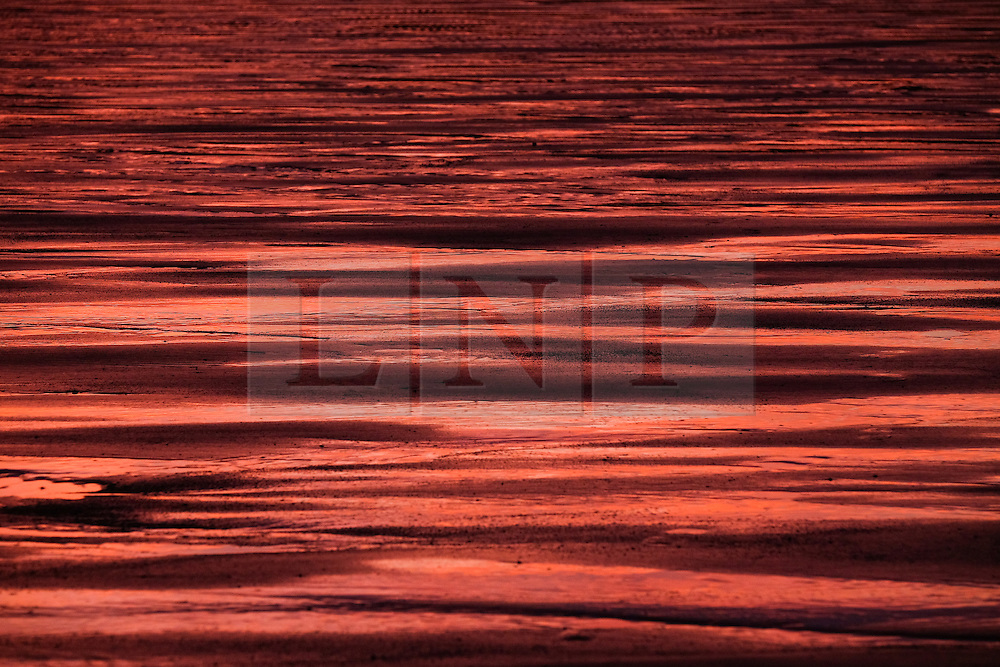 &copy; Licensed to London News Pictures.11/10/15<br /> Saltburn, UK. <br /> <br /> A fiery Autumn sunrise is reflected on wet sand on the beach at Saltburn by the Sea in Cleveland.<br /> <br /> Photo credit : Ian Forsyth/LNP