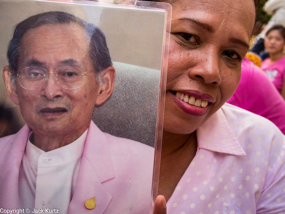 01 AUGUST 2013 - BANGKOK, THAILAND: A woman holds up a picture of Bhumibol Adulyadej, the King of Thailand, in front of Siriraj Hospital, before the King left the hospital Thursday. The King, 85, was discharged from Bangkok's Siriraj Hospital, where he has lived since September 2009. He traveled to his residence in the seaside town of Hua Hin, about two hours drive south of Bangkok, with his wife, 80-year-old Queen Sirikit, who has also been treated in the hospital for a year.      PHOTO BY JACK KURTZ