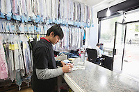 Young male employee and tailor working at dry cleaning shop