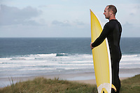 Man holding surfboard on hill looking at sea side view