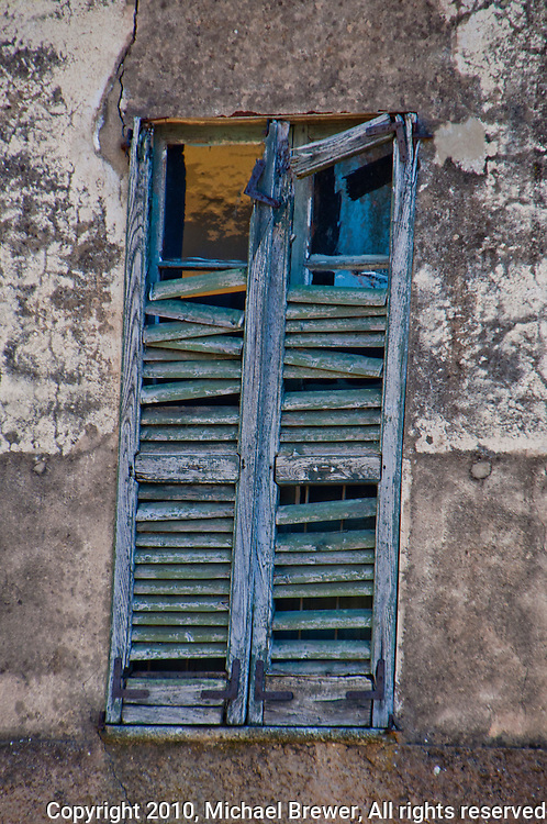 Old decaying,  window with broken blue shutters in Mendrisio, Ticino, Switzerland.
