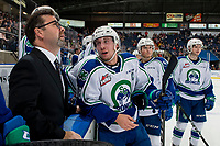 KELOWNA, BC - OCTOBER 16:  Head coach Dean Brockman watches the replay as Ethan Regnier #18 of the Swift Current Broncos stands at the bench against the Kelowna Rockets at Prospera Place on October 16, 2019 in Kelowna, Canada. (Photo by Marissa Baecker/Shoot the Breeze)