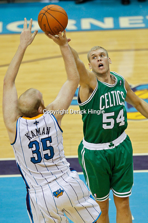 December 28, 2011; New Orleans, LA, USA; New Orleans Hornets center Chris Kaman (35) shoots over Boston Celtics center Greg Stiemsma (54) during the fourth quarter of a game at the New Orleans Arena. The Hornets defeated the Celtics 97-78.  Mandatory Credit: Derick E. Hingle-US PRESSWIRE