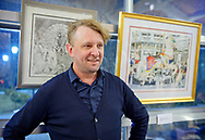 Garden City, New York, USA. March 9, 2019.  Artist Michael White is standing by his carousel watercolor prints for sale during Unveiling Ceremony of his mural of Nunley's Carousel horse closeup. Event was held at historic Nunley's Carousel in its Pavilion on Museum Row on Long Island.