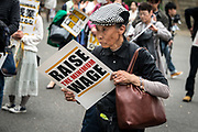 An hold protester holds a placard demanding a higher wage in Tokyo April 15, 2017, Japan. A Group of young people named Aequitas who means Equity in Latin, organised a demonstration to demanded a minimum hourly wage of 1,500 JPY (approx. USD 13.7), currently the minimum wage ranges from 700 to 900 JPY (approx. USD from 6,4 to 8,3). 15/04/2017-Tokyo, JAPAN