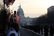 A Barack Obama inauguration attendee looks out at police lined Pennsylvania Avenue.