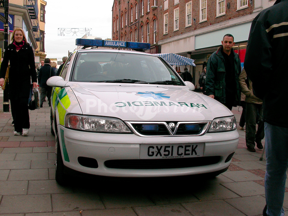 Paramedic ambulance car in busy shopping precinct outside Boots chemist; UK