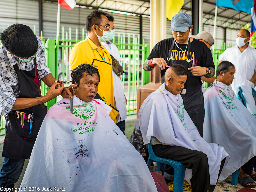 25 JUNE 2016 - BANGKOK, THAILAND:  People get free haircuts from a barber school on the platforms in Hua Lamphong train station. The station opened on June 25, 1916 after six years' construction. The station was built in an Italian Neo-Renaissance-style, with decorated wooden roofs and stained glass windows. The architecture is attributed to Turin-born Mario Tamagno. There are 14 platforms, 26 ticket booths, and two electric display boards. Hua Lamphong serves over 130 trains and approximately 60,000 passengers each day. Since 2004 the station has been connected by an underground passage to the MRT (Metropolitan Rapid Transit) subway system's Hua Lamphong Station.     PHOTO BY JACK KURTZ
