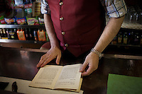 """AFFILE, ITALY - 23 AUGUST 2012: Luciano Battiglieri, 52, owner of Bar San Sebastiano, flips through the pages of a book on fascist Marsall Rodolfo Graziani in Affile, a town with a population of 1,600 80km east of Rome, on August 23, 2012. A mausoleum and park, dedicated to the memory of Fascist Field Marshall Rodolfo Graziani, has recently been opened in the Italian town of Affile. At a cost of €127,000 to local taxpayers, the mayor Ercole Viri has expressed hope that the site will become as 'famous and as popular as Predappio' – the burial place of Mussolini which has become a shrine to neo-Fascists. Rodolfo Graziani was the youngest colonel in the Regio Esercito (Royal Italian Army), known as the """"Butcher of Fezzan"""" and the """"Butcher of Ethiopia"""" for the brutal military campaigns and gas attacks he led in Libya and Ethiopia under the dictatorship of Benito Mussolini under which he then became Minister of Defence from 1943 to 1945."""