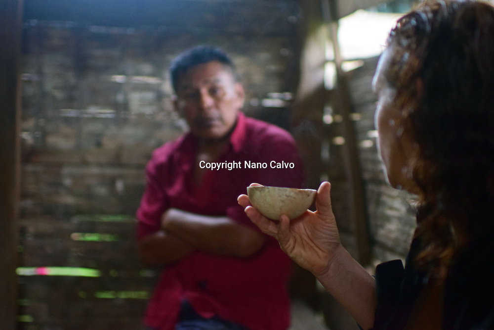 Karine drinks cacao while talking with Catato, after preparing natural cacao drink at Bribri tribe house. <br />