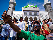 "15 JUNE 2018 - SEOUL, SOUTH KOREA: A Muslim African worker in Seoul takes a ""selfie"" with a smart phone at Seoul Central Mosque on Eid al Fitr, the Muslim Holy Day that marks the end of the Holy Month of Ramadan. There are fewer than 100,000 Korean Muslims, but there is a large community of Muslim immigrants in South Korea, most in Seoul. Thousands of people attend Eid services at Seoul Central Mosque, the largest mosque in South Korea.   PHOTO BY JACK KURTZ"