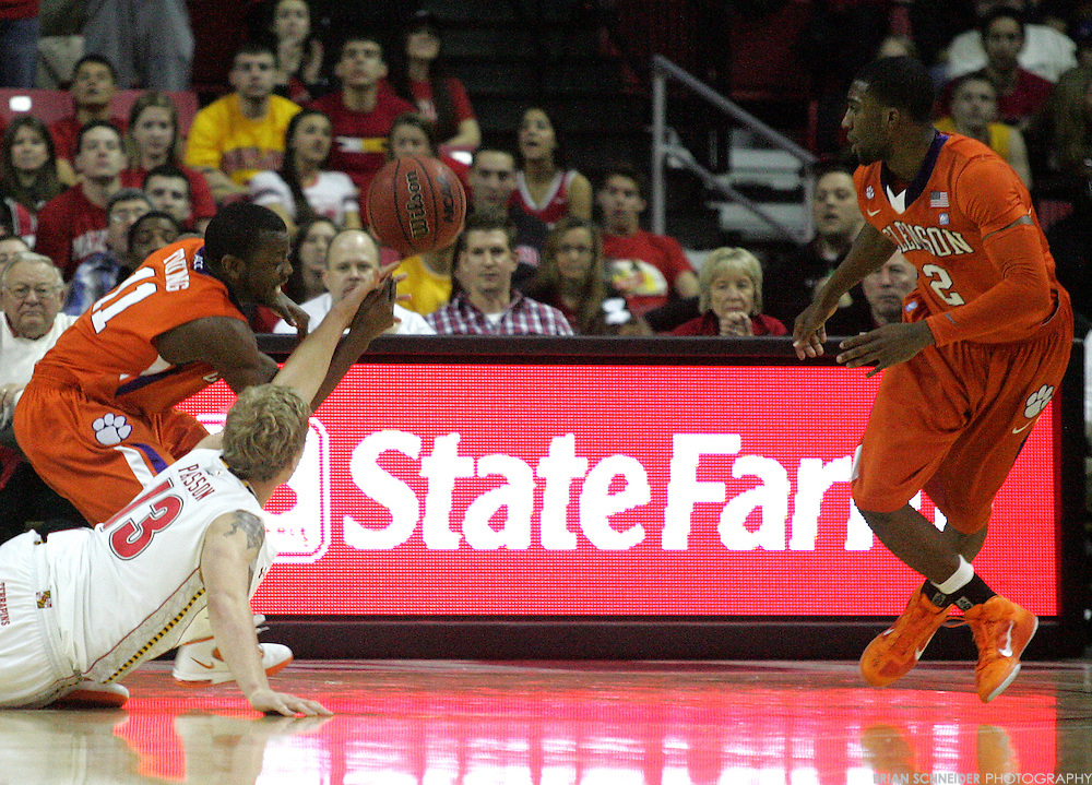 Jan 22, 2011; College Park, MD, USA; Clemson Tigers guard Andre Young (11) and guard Demontez Stitt (2) and Maryland Terrapins forward Haukur Palsson (13) go for a loose ball during the second half at the Comcast Center. Mandatory Credit: Brian Schneider-www.ebrianschneider.com