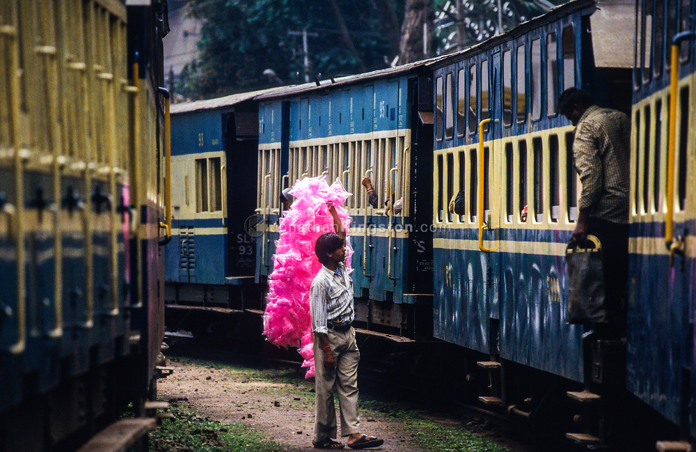 A cotton candy vendor touts his wares for passengers of The Nilgiri Mountain Railway in Coonoor.  The railway is one of the oldest mountain railways in India and a UNESCO world heritage site, connects the town of Ootacamund with the town of Mettupalayam in the foothills of the Western Ghats, Tamil Nadu, India.