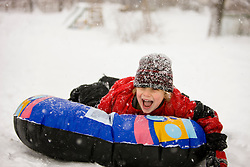 A young boy sledding on a snow tube during a snowstorm in Portsmouth, New Hampshire.