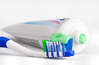 Closeup of a toothbrush with dental paste and tube. Macro shot with use of selective focus. All logos removed.