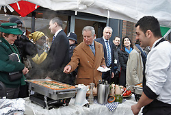 © Licensed to London News Pictures.  27/01/2012. LONDON, UK. Prince Charles (pictured centre) tries Italian food, including a homemade pesto, prepared by Alessio Garau, 29 (pictured right) during a visit to Lower Marsh market near Waterloo. The Prince was visiting with Kirsty Allsopp (pictured back right) as part of a event for the Prince's Foundation for the Built Environment. Photo credit :  Cliff Hide/LNP