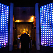 TOKYO, JAPAN - JULY 7 : Koukokuji temple chief priest Yajima Taijun pray at the altar inside the Ruriden columbarium as glass Buddha alters are lit up on July 7, 2016 in Tokyo, Japan. Operated by the Koukokuji buddhist temple, The Ruriden columbarium at the Koukoko-ji Temple houses over 2,046 crystal Buddha statues, each illuminated by high-powered LED lights. Behind each Buddha is a drawer storing people's ashes. An IC card allows the owner of the alter to access the building and lights up the corresponding statue. The ashes are stored for 33 years before being buried below the Ruriden, currently 900 alters are in use as of July 2016. (Photo: Richard Atrero de Guzman/NUR Photo)