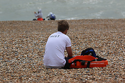 © Licensed to London News Pictures. 04/07/2014. Brighton, UK. A man on Brighton beach. Rain and clouds has stopped most people from visiting the South Coast while rough seas dettered people from swimming. Photo credit : Hugo Michiels/LNP