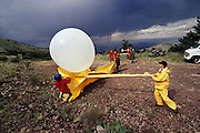 Launching weather balloon with field mills into an approaching electrical lightning storm.. Langmuir Atmospheric Research Lab on Mt. Baldy, New Mexico (1992) Lightning occurs when a large electrical charge builds up in a cloud, probably due to the friction of water and ice particles. The charge induces an opposite charge on the ground, and a few leader electrons travel to the ground. When one makes contact, there is a huge backflow of energy up the path of the electron. This produces a bright flash of light, and temperatures of up to 30,000 degrees Celsius..