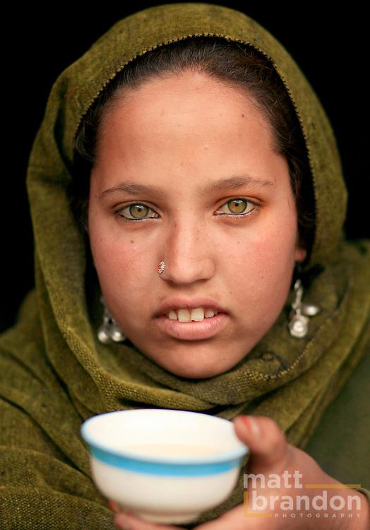 A green eyed Gujjar girl with a cup of salt tea. Lidderwat, Kashmir, India
