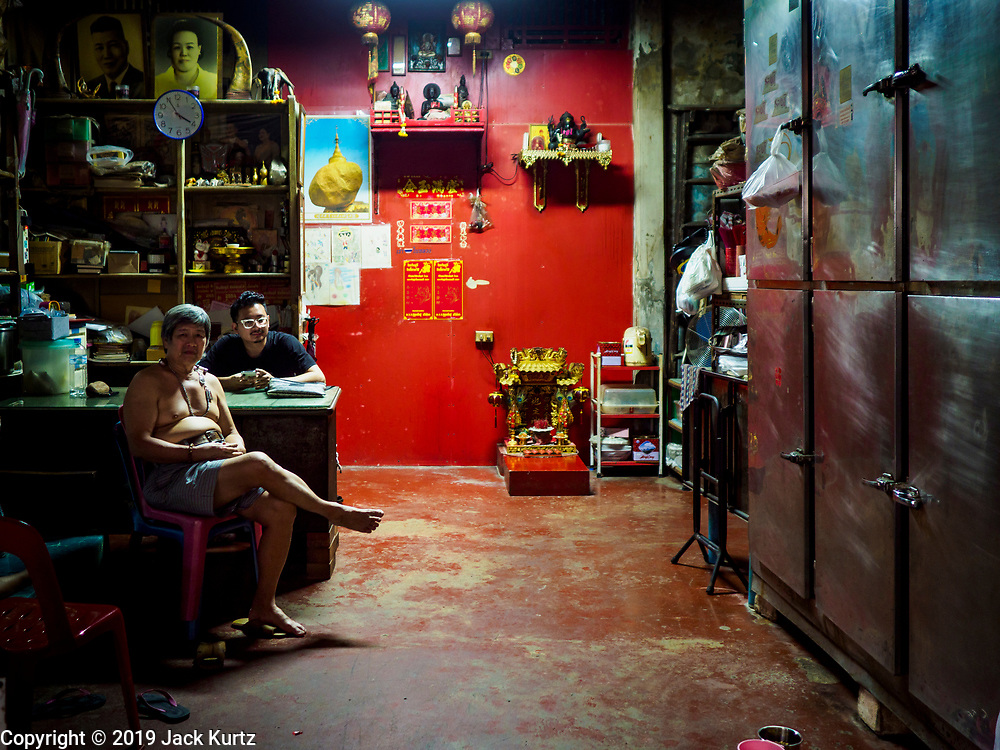 "26 FEBRUARY 2019 - BANGKOK, THAILAND: Men in their shophouse in a market in Bangkok's Chinatown. Bangkok has one of the largest ""Chinatown"" districts in the world. About 14% of all Thais have some Chinese ancestry and Chinese cultural practices are incorporated in many facets of Thai daily life.       PHOTO BY JACK KURTZ"