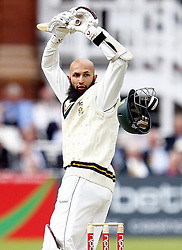 South Africa's Hashim Amla looks back at his helmet after getting a bouncer from England's James Anderson during The First npower Test match at Lord's Cricket Ground, London.
