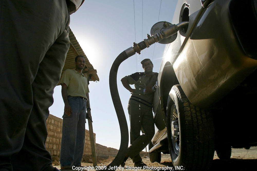 Emad Al-Kasid, far left, smiles as a driver fills his GMC Suburban with gas in Al Quim, Iraq, as the family finally clears the Syrian-Iraqi border at about 8:30a.m. Sunday, July 20, 2003. The family is travelling back to its home city of Nassiriyah, Iraq, for the first time since 1991 after fighting in the failed uprising against Saddam Hussein, fleeing to a refuge camp in Saudi Arabia for 3 years and finally settling in Dearborn, MI.