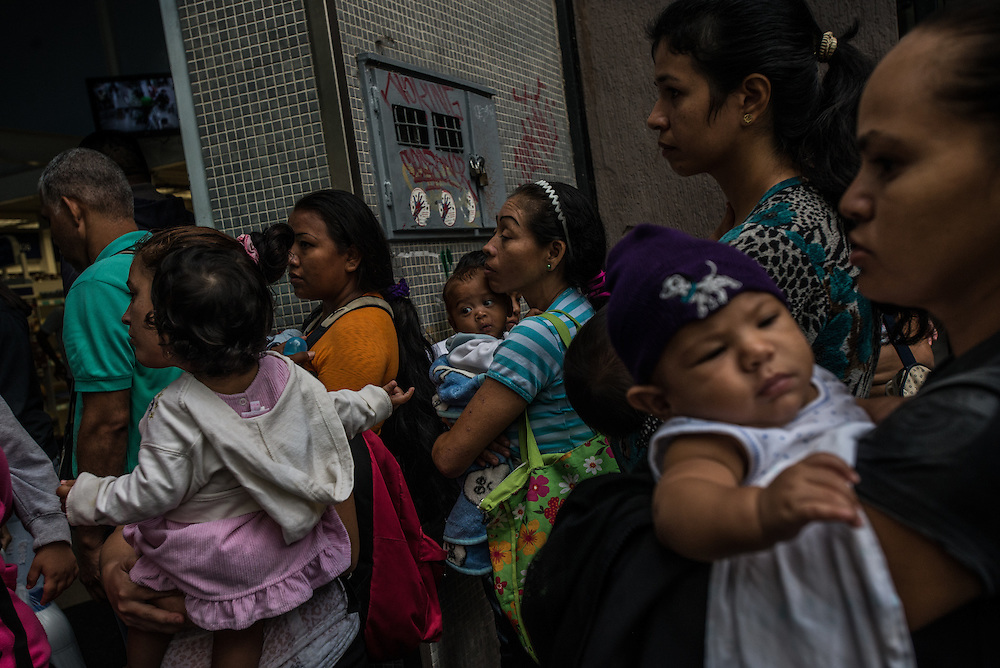 CARACAS, VENEZUELA - APRIL 6, 2016: Hundreds of people wait in line just after dawn outside of a pharmacy in hopes of being able to buy price-controlled diapers and formula. After a decade of an oil bonanza marked by subsidies and social programs, Venezuela&rsquo;s economy is contracting for the third straight year. Its inflation, the world&rsquo;s highest, is expected to rise to nearly 500 percent.<br />