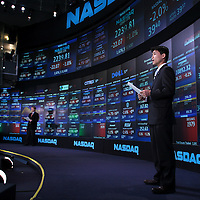 Journalists report the day's business news from the NASDAQ Marketsite in Times Square, NY.