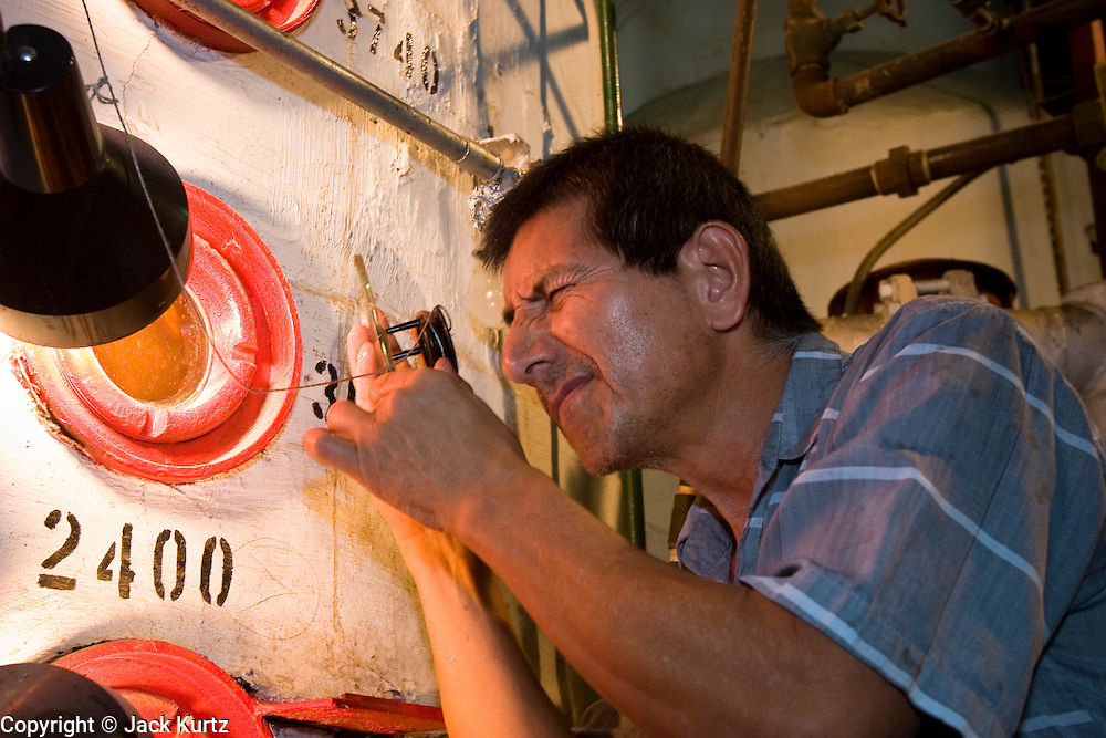 15 NOVEMBER 2005 - FRANKLIN, LA: RUDOLFO ROJAS, a sugar boiler at the St. Mary Sugar Co-Op Mill near Franklin, Louisiana, checks the quality of sugar cane syrup during the 2005 sugar cane harvest. Louisiana is one of the leading sugar cane producing states in the US and the economy in southern Louisiana, especially St. Mary and Iberia Parishes, is built around the cultivation of sugar. The mill employs about 180 people. The two mills near Franklin contribute about $150 million (US) to the local economy. Sugar growers in the area are concerned that trade officials will eliminate sugar price supports during upcoming trade talks for the proposed Free Trade Area of the Americas (FTAA). They say elimination of price supports will devastate sugar growers in the US and the local economies of sugar growing areas. They also say it will ultimately lead to higher sugar prices for US consumers. PHOTO BY JACK KURTZ