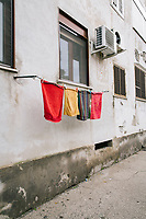 """NAPLES, ITALY - 2 FEBRUARY 2019:  Towels hand in front of a window in the Rione Luzzatti, the neighborhood in which Elena Ferrante's """"My Brilliant Friend"""" is set, in Naples, Italy, on February 2nd 2019.<br /> <br /> In December 2018, City Sightseeing - the world's largest sightseeing tour bus operator - inaugurated the """"Brilliant Naples"""" tour, inspired by the locations in """"Neapolitan Novels"""", a 4-part series by the Italian novelist Elena Ferrante. The series has sold over 10 million copies in 40 countries. The first book in the series has also been adapted into an HBO television series entitled, """"My Brilliant Friend."""""""
