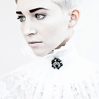 Close up of young woman with short white hair wearing broach and lace  looking to side