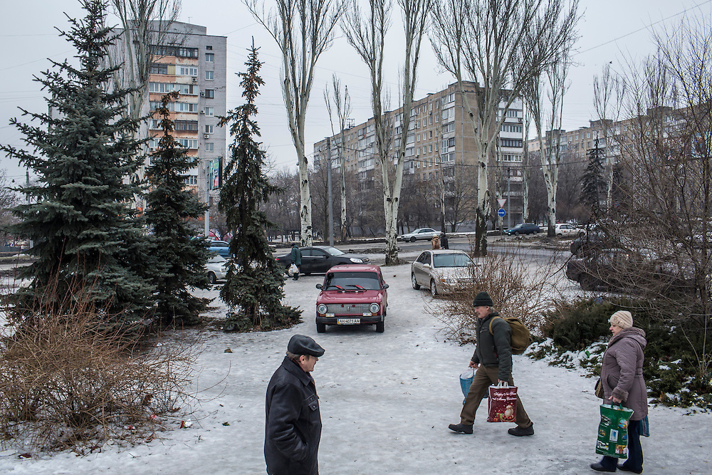 DONETSK, UKRAINE - JANUARY 29, 2015: People carry bags of food distributed to needy residents by the Rinat Akhmetov Fund outside a supermarket in Donetsk, Ukraine. The food distribution drew heavy crowds as many people are no longer paid a salary or have had difficulty accessing bank accounts. CREDIT: Brendan Hoffman for The New York Times