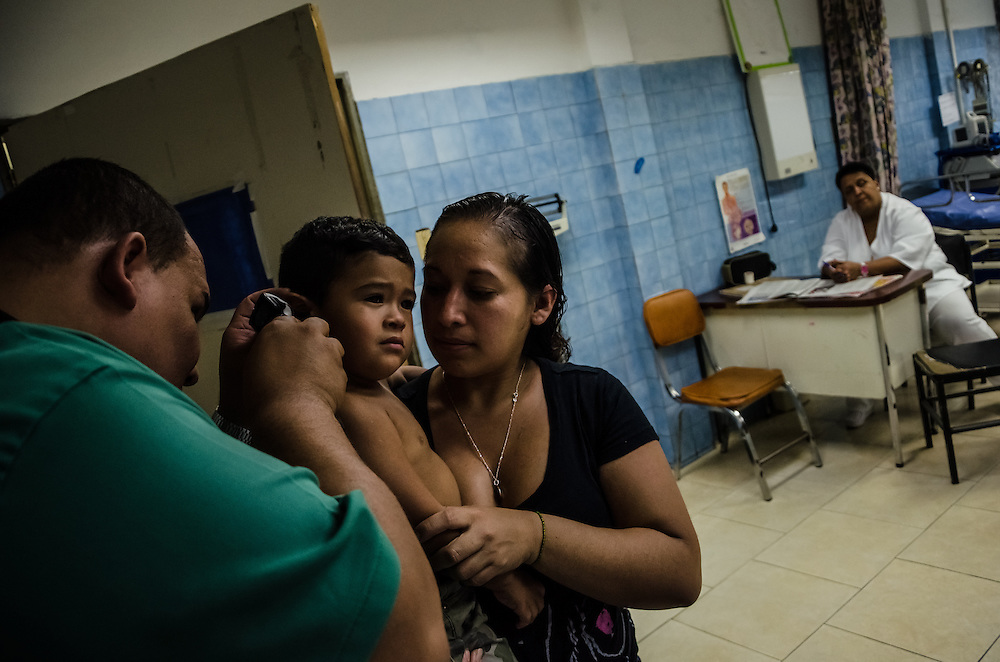 CARACAS, VENEZUELA - JANUARY 21, 2015: A doctor examines a boy brought to the emergency room of the state hospital in the Petare slum in Caracas. Doctors here say they are working with a bare minimum of supplies, and often have to turn patients away. Despite being a petro-state with one of the largest oil reserves in the world, basic and advanced medical supplies from gauze and surgical gloves, to heart stints, are difficult to find in hospitals and pharmacies across Venezuela.
