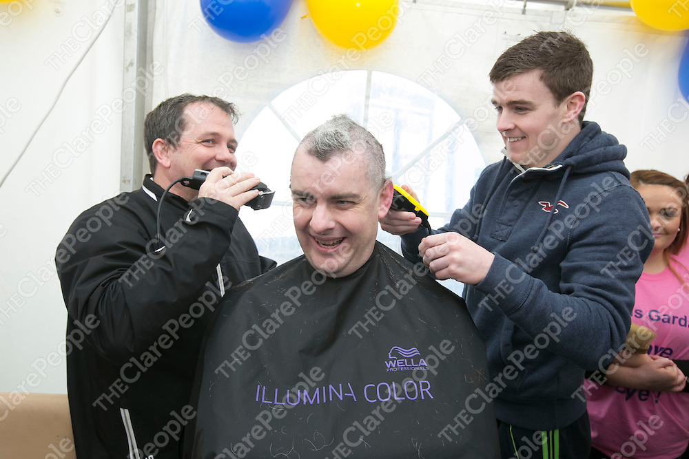 Clare Manager Davy Fitzgerald &amp; Clare's Tony Kelly shave the Head of Sargent  Mark Murphy  at  the Garda Shave or Dye event in O'Connell Square Ennis. .<br /> Pictured Credit Brian Gavin Press 22