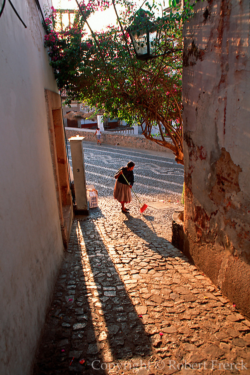 MEXICO, COLONIAL CITIES, TAXCO woman sweeping the winding cobblestone streets in the old colonial part of town